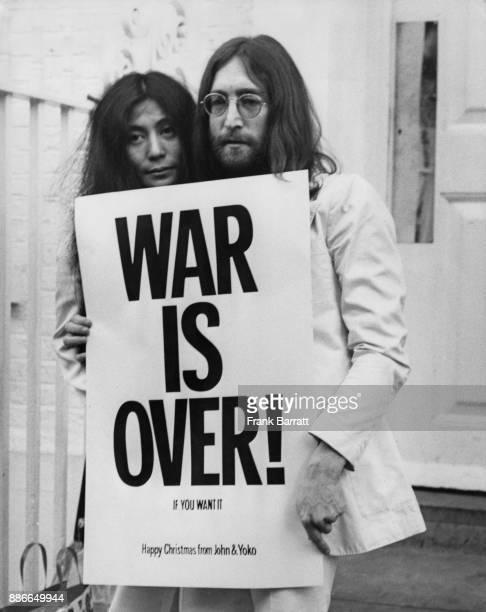 Singer and songwriter John Lennon formerly of English rock band the Beatles and his wife Yoko Ono pose on the steps of the Apple building in London...