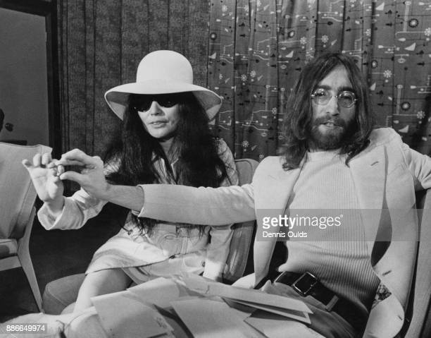 Singer and songwriter John Lennon of English rock band the Beatles and his wife Yoko Ono holding acorns during a press conference at Heathrow Airport...