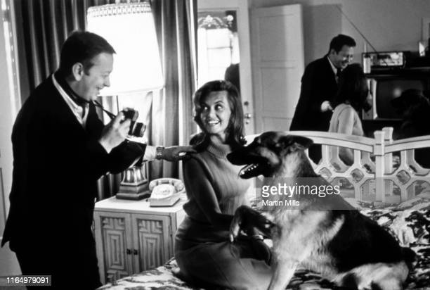 Singer and songwriter Mel Torme takes pictures of his wife English actress Janette Scott and their German Shepherd at their home circa 1965 in Los...
