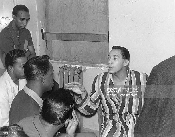 Singer and songwriter Smokey Robinson rehearses a song with the Temptations in their dressing room at the Apollo Theater in 1964