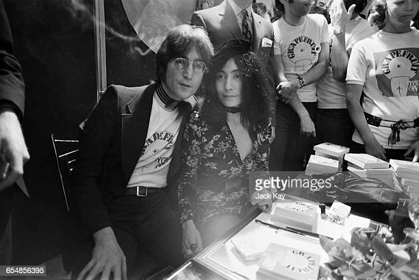 Singer and songwriterJohn Lennon with his wife Yoko Ono signing copies of her conceptual art book 'Grapefruit' at Selfridges London 15th July 1971