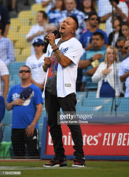 Singer Andy Vargas performs the National Anthem before the game between the Los Angeles Dodgers and the Miami Marlins at Dodger Stadium on July 20...