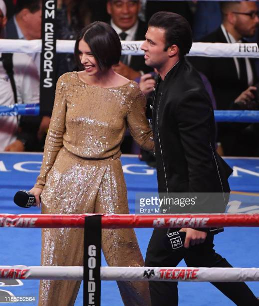 Singer Angela Aguilar and singer/actor Jencarlos Canela leave the ring after Aguilar sang the Mexican national anthem and Canela performed the...