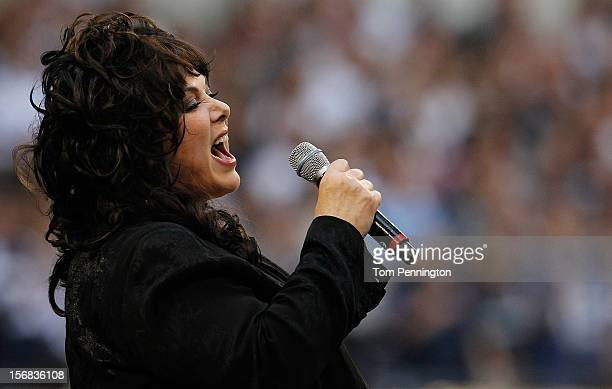 Singer Ann Wilson performs the national anthem before the Dallas Cowboys take on the Washington Redskins on Thanksgiving Day at Cowboys Stadium on...