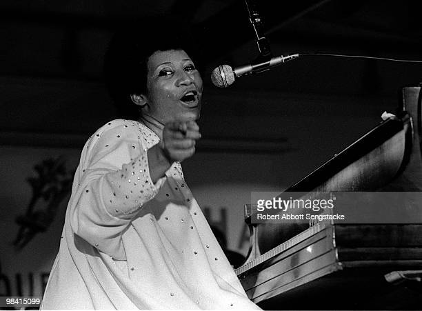 Singer Aretha Franklin points to the audience while singing and playing the piano during a concert at Chicago's Cook County Jail ca1970s