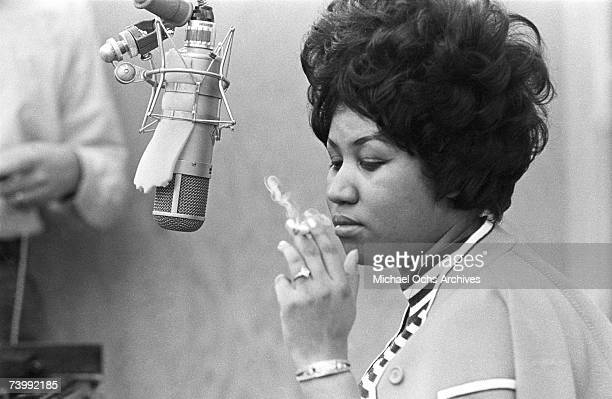 Singer Aretha Franklin smokes as cigarette as she works in the studio by a microphone at Muscle Shoals Studios on January 9 1969 in Muscle Shoals...