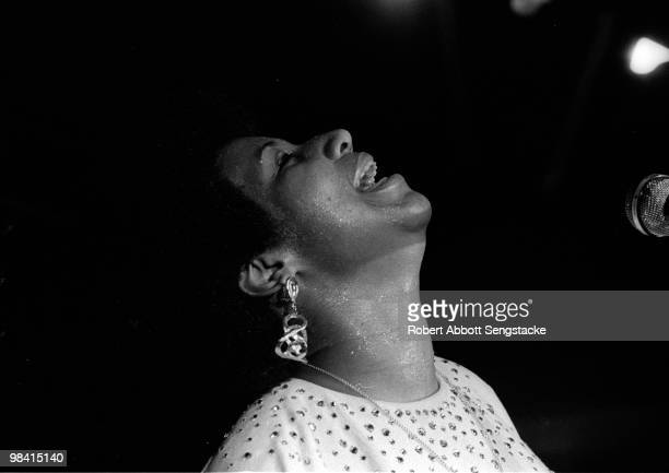 Singer Aretha Franklin tilts her head back in a joyful pose while singing and playing the piano during a concert at Chicago's Cook County Jail ca1970s