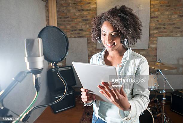 Singer at a recording studio holding a tablet computer