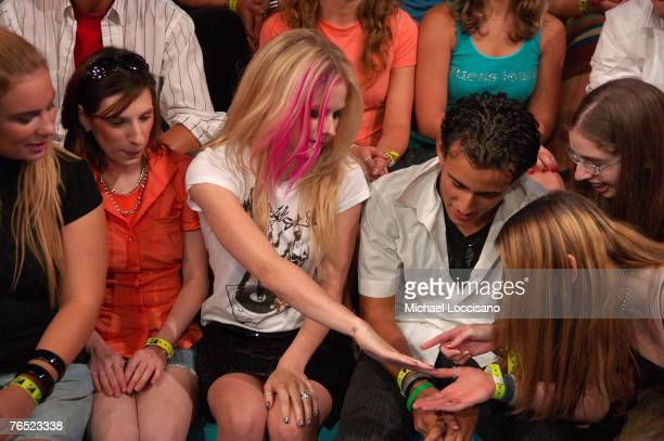 """Singer Avril Lavigne shows fans her engagement and wedding rings during her appearance on MTV's """"TRL"""" at MTV Studios in New York City's Times Square..."""