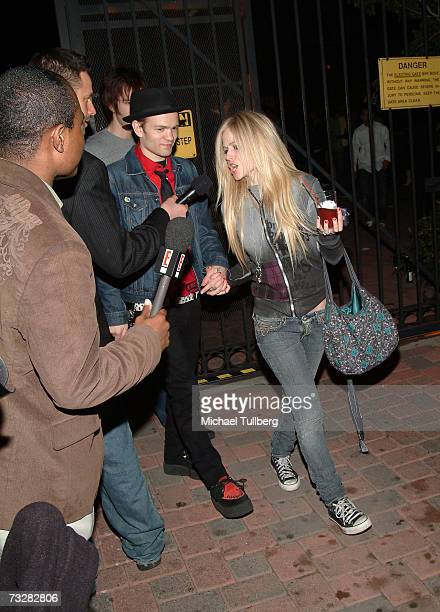 Singer Avril Lavigne yells at a TV camera crew as she exits with husband Deryck Whibley from the 10th annual Friends And Family Grammy event held at...