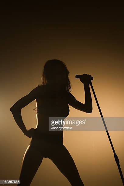 singer backlit with microphone on the big stage - big mike stock pictures, royalty-free photos & images