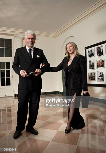 Singer Barbra Streisand pulls on her husband actor James Brolin's arm while arriving at the White House for a state dinner 19 2011 in Washington DC...