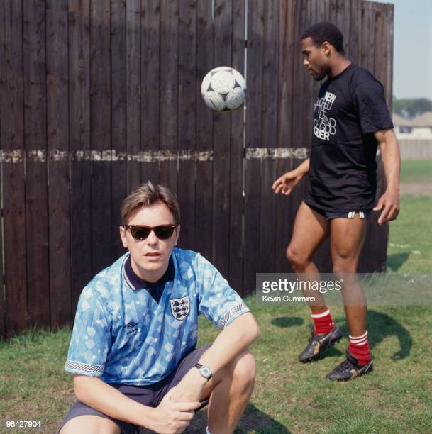 Singer Bernard Sumner of English rock group New Order with footballer John Barnes whilst filming the video for the official song of the England...