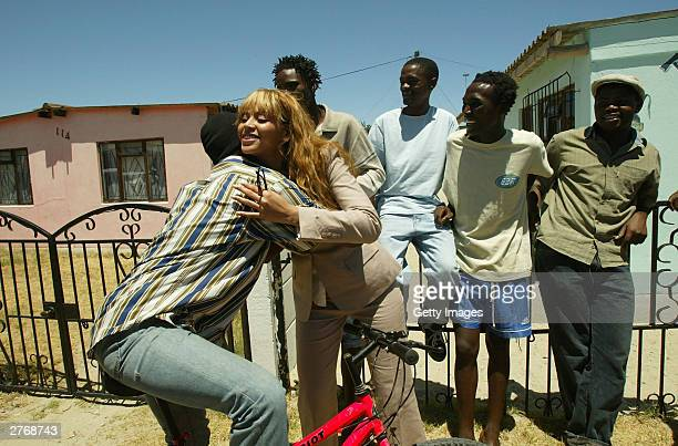 Singer Beyonce Knowles meets local people outside the Baphumelele orphanage for children with AIDS whose parents have died of AIDS prior to the 46664...