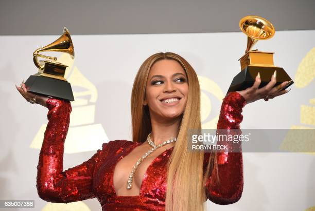 Singer Beyonce poses with her Grammy trophies in the press room during the 59th Annual Grammy music Awards on February 12 in Los Angeles California /...