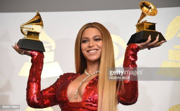 Singer Beyonce poses with her Grammy trophies in the press room during the 59th Annual Grammy music Awards on February 12 in Los Angeles, California....