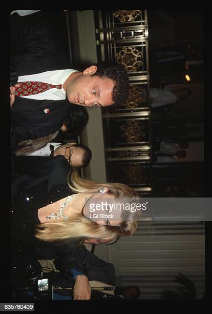 Singer Billy Joel and his model wife Christie Brinkley walk up a stairway at a formal function