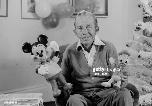 Singer Bing Crosby holding Mickey Mouse and Donald Duck dolls during filming for the Christmas special of the BBC television show 'Disney Time',...