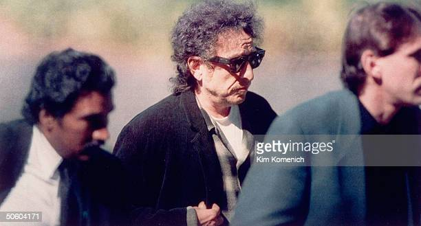 Singer Bob Dylan wearing sunglasses and looking distraught on his way to the funeral of rock star Jerry Garcia