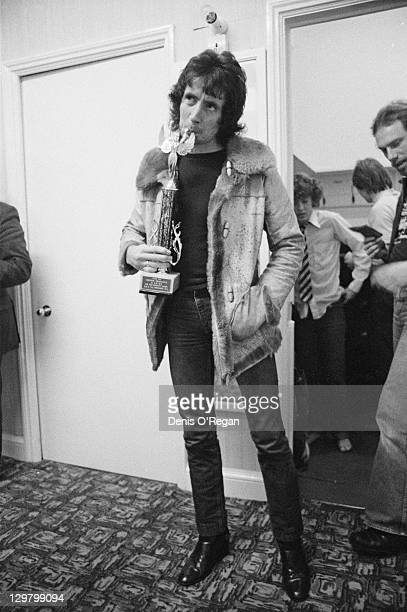 Singer Bon Scott of rock group AC/DC holding an award trophy backstage at the Gaumont Southampton during the Highway To Hell UK tour 1979