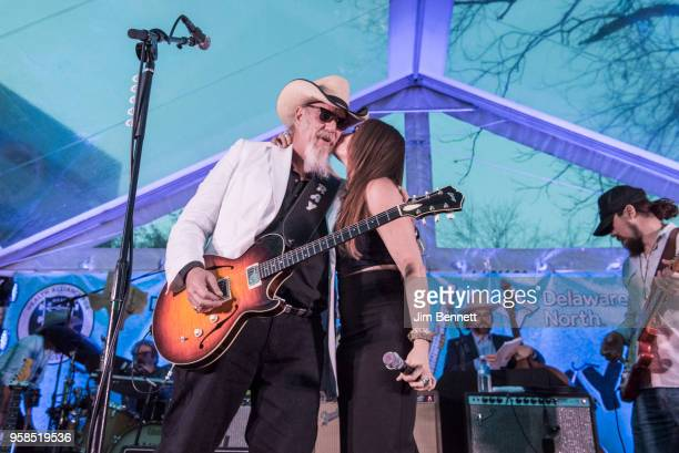 Singer Bonnie Bishop kisses lead guitarist and vocalist Ray Benson of Asleep At The Wheel on the cheek during a live performance on stage at Ray's...