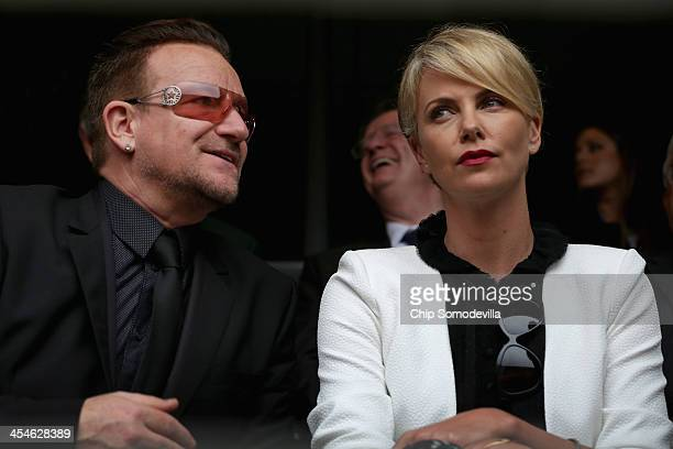 Singer Bono and South African actor Charlize Theron arrive for the official memorial service for former South African President Nelson Mandela at FNB...