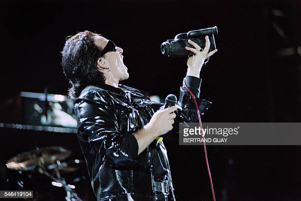 """Singer Bono holds a camera during the U2 concert at Vincennes racetrack on June 26 part of the U2 """"Zoo TV Tour"""". / AFP / BERTRAND GUAY"""