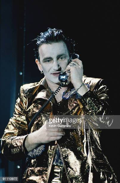 Singer Bono makes a phone call in his stage persona of Mr MacPhisto during a concert by Irish rock group U2 on their 'Zoo TV' tour 1992