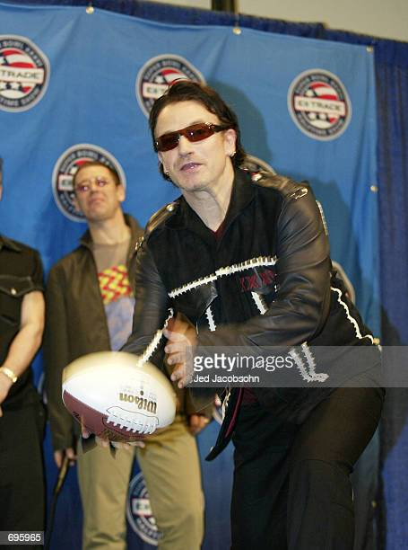 U2 singer Bono tosses a football to a member of the media while bassist Adam Clayton looks on during the Super Bowl XXXVI ETrade Halftime press...