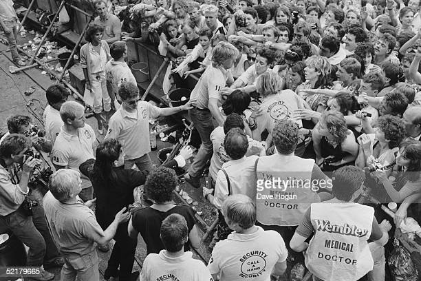 U2 singer Bono watching medical staff remove a fan from the front of the Live Aid crowd at Wembley 13th July 1985