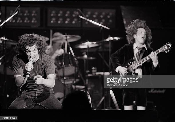 Singer Brian Johnson and guitarist Angus Young performing with heavy rock group AC/DC on tour in the UK 1981 In the background is drummer Phil Rudd...