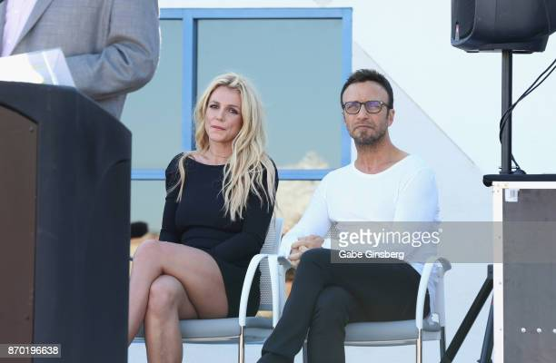 Singer Britney Spears and talent manager Larry Rudolph listen to Clark County Commissioner Steve Sisolak's speech during the grand opening of the...
