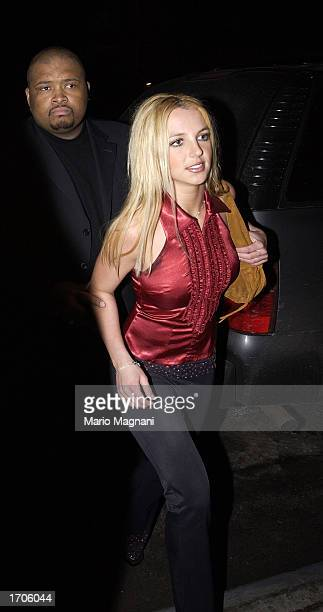 Singer Britney Spears arrives at her New Year's Eve party at the Hudson Hotel escorted by a bodyguard December 31 2002 in New York City