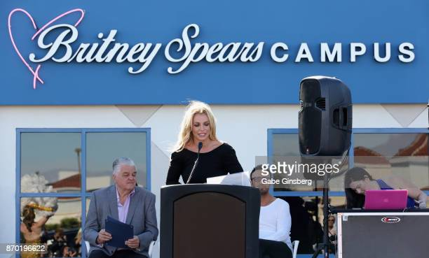 Singer Britney Spears speaks as Clark County Commissioner Steve Sisolak and talent manager Larry Rudolph look on during the grand opening of the...
