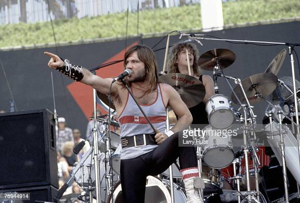 Singer Bruce Dickinson of the metal band 'Iron Maiden' points to the crowd as the drummer Clive Burr plays behind him at The Oakland Coliseum in...