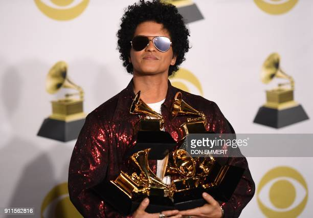 Singer Bruno Mars poses in the press room with his Grammy trophies during the 60th Annual Grammy Awards on January 28 in New York / AFP PHOTO / Don...