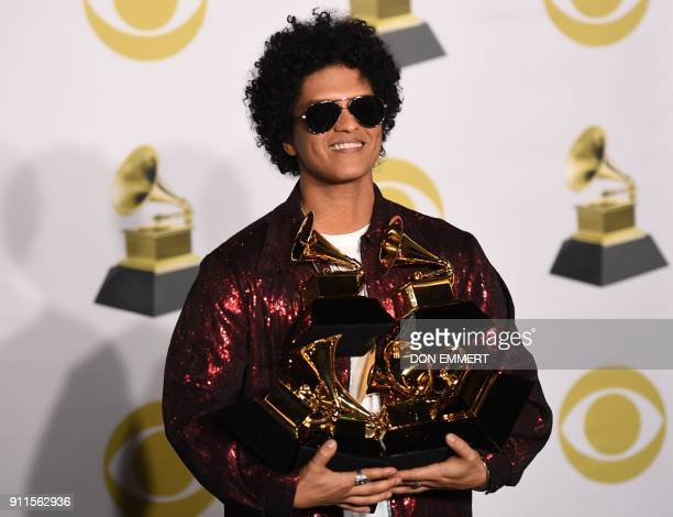TOPSHOT Singer Bruno Mars poses in the press room with his Grammy trophies during the 60th Annual Grammy Awards on January 28 in New York / AFP PHOTO...