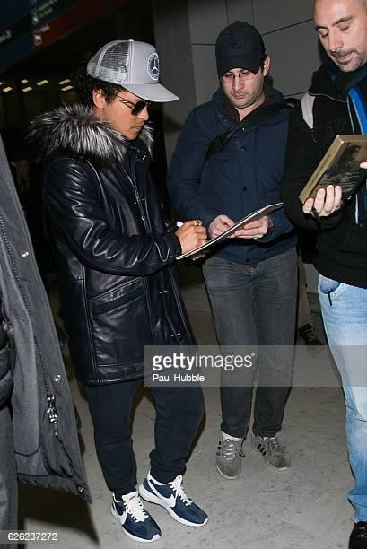 Singer Bruno Mars signs autographs as he arrives at Aeroport Roissy Charles de Gaulle on November 28 2016 in Paris France
