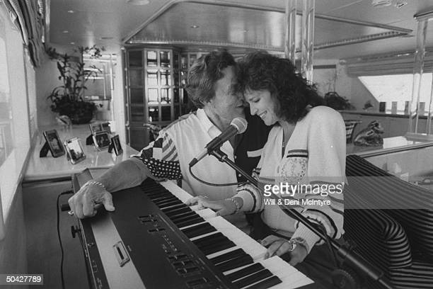 C/W singer businessman Jimmy Dean nuzzling his fiancee singer Donna Meade as she plays electronic keyboard on his spacious yacht Big Bad John