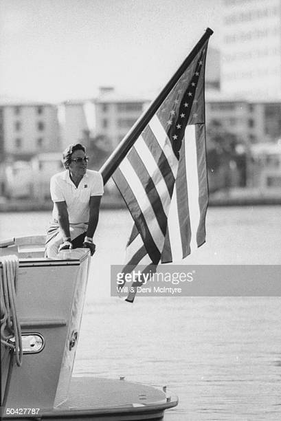 C/W singer businessman Jimmy Dean posing on the rail next to an American flag on pole at the stern of his yacht