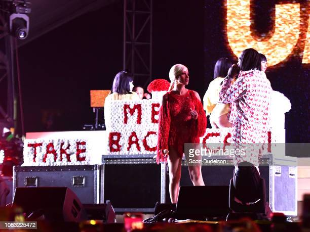 Singer Cardi B is presented a 'Take Me Back' card onstage by Offset during day 2 of the Rolling Loud Festival at Banc of California Stadium on...
