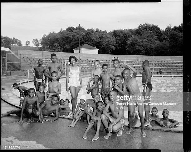 Singer Carol Thompson posing with boys including Sherman Parker on left Harold Wilkes on right Louis Murrell Jr on right in pool and Donald 'Muscles'...