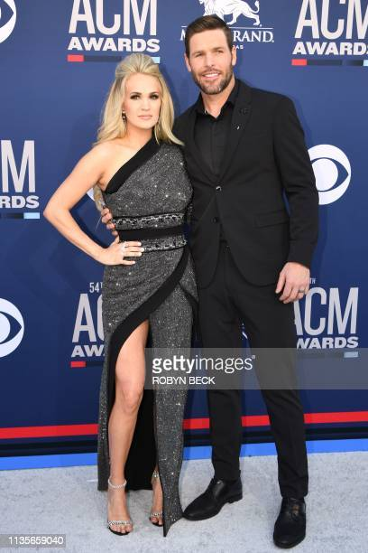 US singer Carrie Underwood and husband CanadianUS former ice hockey player Mike Fisher arrive for the 54th Academy of Country Music Awards on April 7...