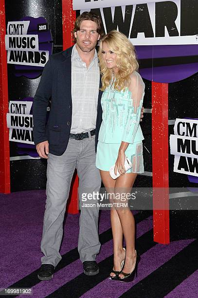 Singer Carrie Underwood and Mike Fisher attend the 2013 CMT Music awards at the Bridgestone Arena on June 5 2013 in Nashville Tennessee