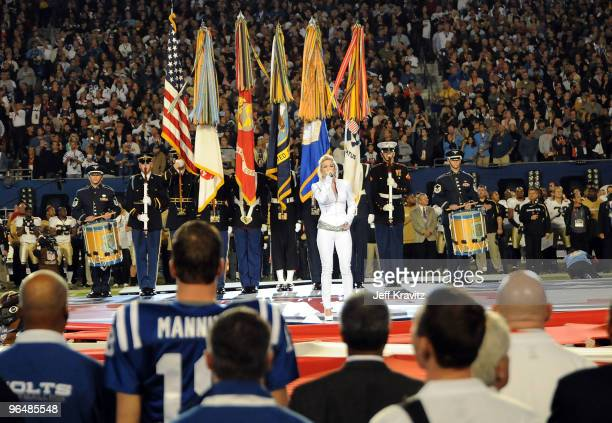 Singer Carrie Underwood performs as Peyton Manning and the Indianapolis Colts look on during the Super Bowl XLIV Pregame Show at Sun Life Stadium on...