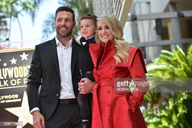 Singer Carrie Underwood poses with her husband Mike Fisher and their 3yearold son Isaiah Michael at her star unveiling ceremony on the Hollywood Walk...