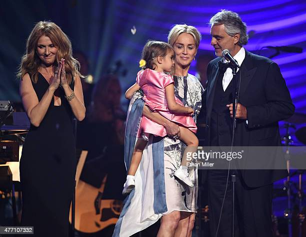 Singer Celine Dion Andrea Bocelli's daughter Virginia Bocelli held by actress Sharon Stone and honoree Andrea Bocelli appear onstage after Dion...