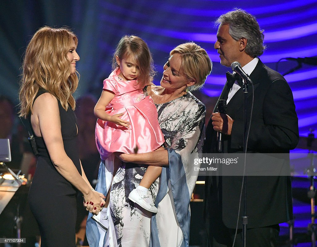 Singer Celine Dion, Andrea Bocelli's daughter Virginia Bocelli, held by actress Sharon Stone, and honoree Andrea Bocelli appear onstage after Dion performed with Bocelli during the 19th annual Keep Memory Alive 'Power of Love Gala' benefit for the Cleveland Clinic Lou Ruvo Center for Brain Health honoring Andrea Bocelli and Veronica Bocelli at MGM Grand Garden Arena on June 13, 2015 in Las Vegas, Nevada.
