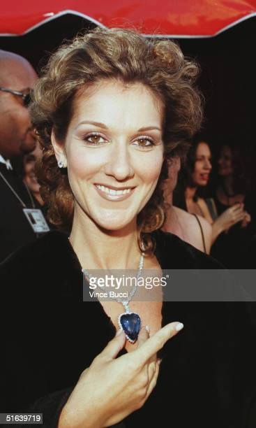 Singer Celine Dion holds a replica of the blue diamond which was aboard the Titanic as she arrives for the 70th Annual Academy Awards 23 March in Los...