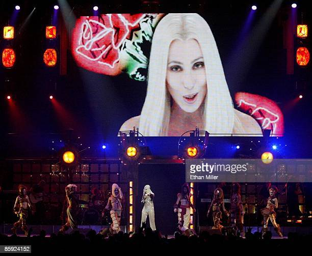 Singer Cher performs with a group of dancers under a video image of herself during the first of two soldout shows as part of her 'Living Proof The...